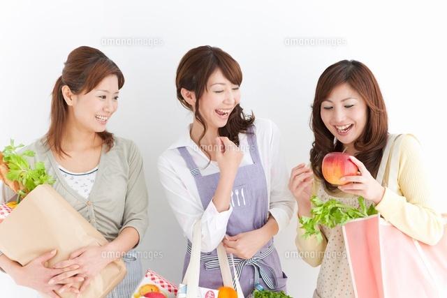 買い物袋を持って会話する主婦3人