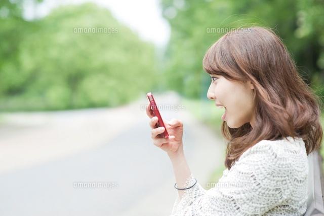 スマートフォンを見て驚く女性 (c)macomoco/a.collectionRF