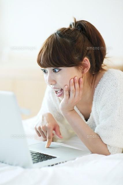 ノートパソコンを操作して驚く女性 (c)macomoco/a.collectionRF