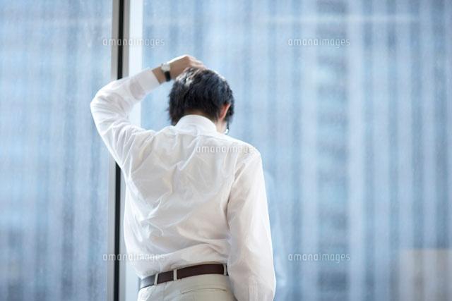窓に寄りかかる男性とビル (c)Doable/a.collectionRF