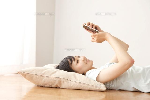 リビングの床でスマートフォンで調べ物をする女性 (c)Doable/a.collectionRF