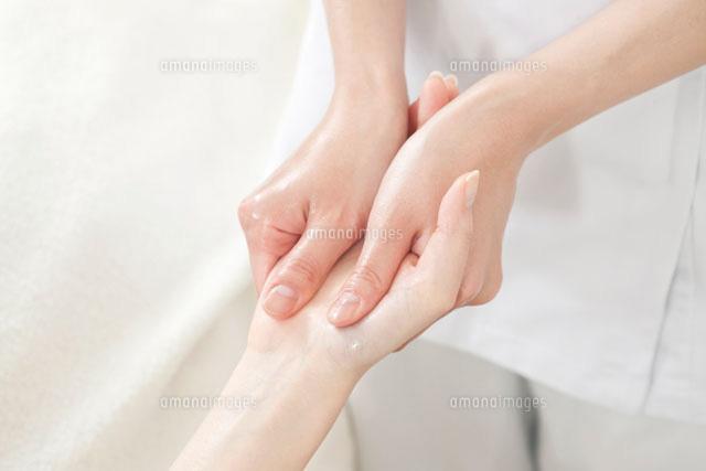 手のマッサージを受ける若い女性 (c)RYO/a.collectionRF