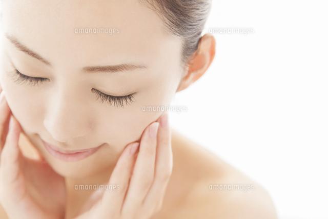 目を閉じ頬に両手を寄せる女性 (c)VGL/a.collectionRF