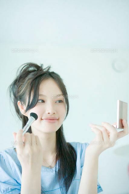 コンパクトミラーを見ながら化粧をする若い女性 (c)absodels RF