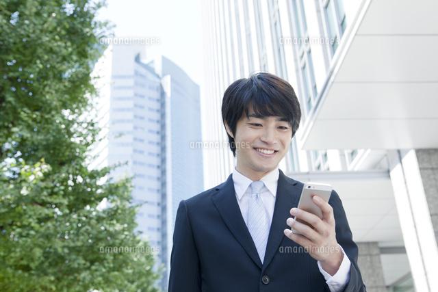 携帯電話を見る笑顔のヤングビジネスマン (c)absodels RF
