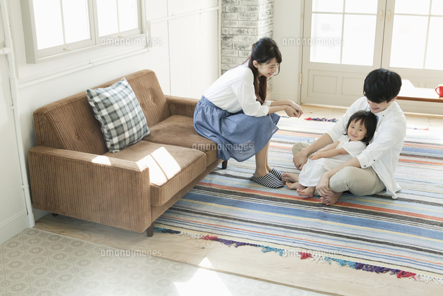 部屋でくつろぐ若い夫婦と子供 (c)absodels RF