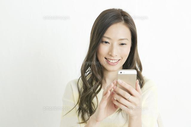 スマホを操作する20代女性 (c)absodels RF