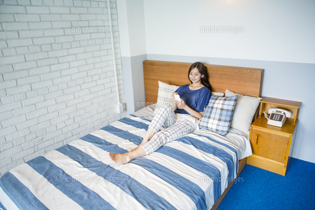 ベッドでスマホを使う20代女性 (c)absodels RF