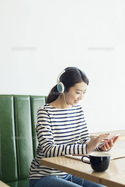 カフェで音楽を聴く20代女性 (c)absodels RF