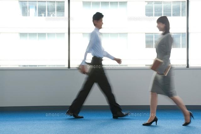 オフィスを歩くビジネスマンとビジネスウーマン (c)moonbase