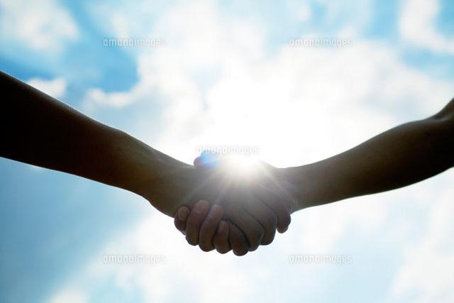 握手する2人の手と太陽 (c)UFO RF/a.collectionRF