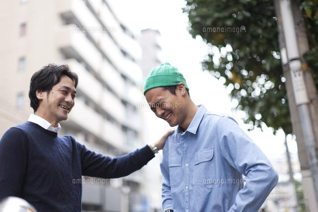 都会の休日に外で談笑する30代男性の友人同士 (c)KIYOKO FUKUDA/a.collectionRF