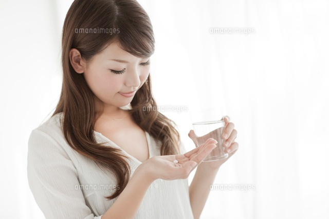 薬と水を持つ若い女性 (c)RYO/a.collectionRF