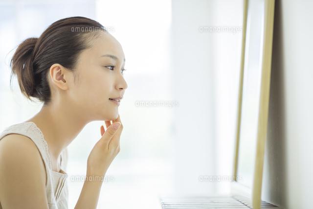 鏡を見て顔に手を触れるスキンケアイメージ (c)RYO/a.collectionRF