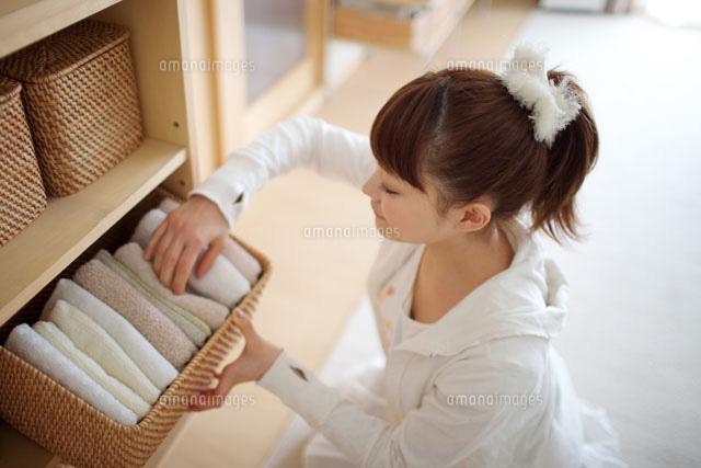 棚の籠からタオルを出す若い女性 (c)MANZO NIIKURA/a.collectionRF
