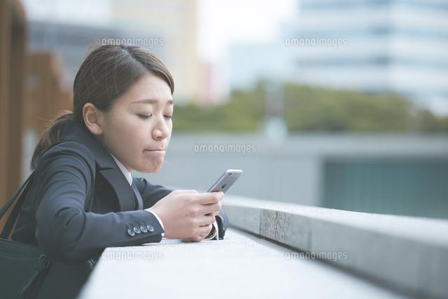 スマホを確認する働く女性 (c)SHAKTI/a.collectionRF