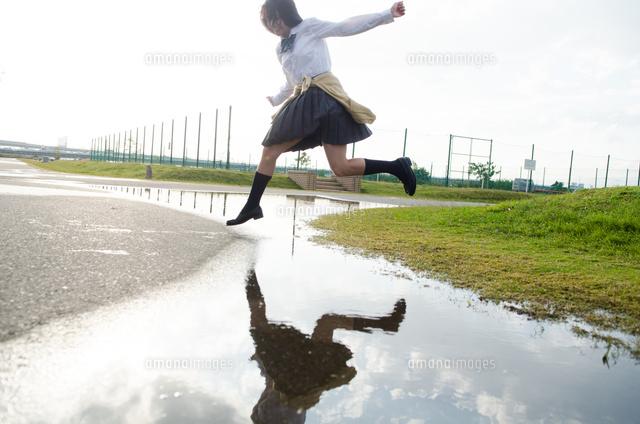 水たまりをジャンプする女子学生 (c)Emi Komagata/a.collectionRF