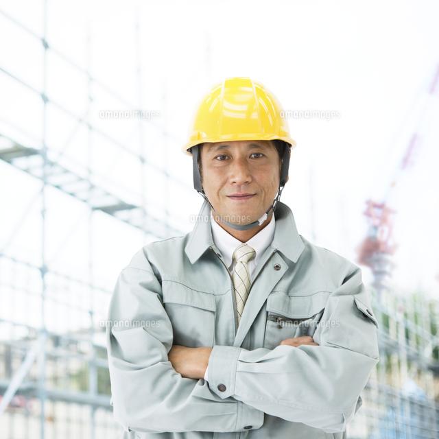 腕を組む工事現場の作業員[11004...
