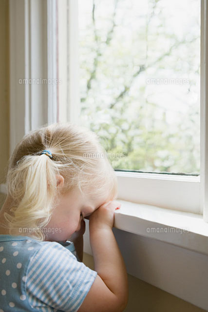 Sad little girl by window (c)Image Source