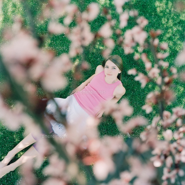 A girl lying on grass looking up at cherry tree blossoms