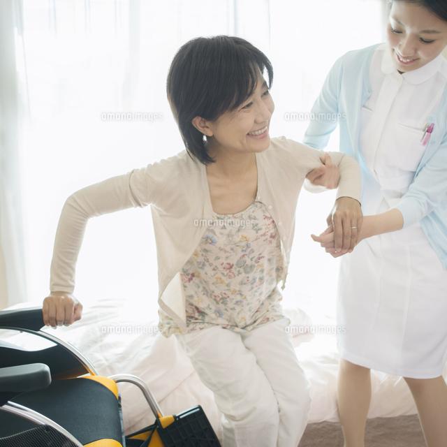 患者の手助けをする看護師(訪問医療) (c)visual supple