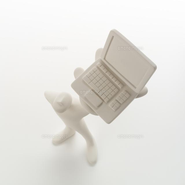 左手にパソコンを掲げて立つ人のオブジェ クラフト (c)visual supple /amanaimages