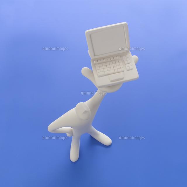 左手にパソコンを掲げて立つ人のオブジェと青 クラフト (c)visual supple /amanaimages