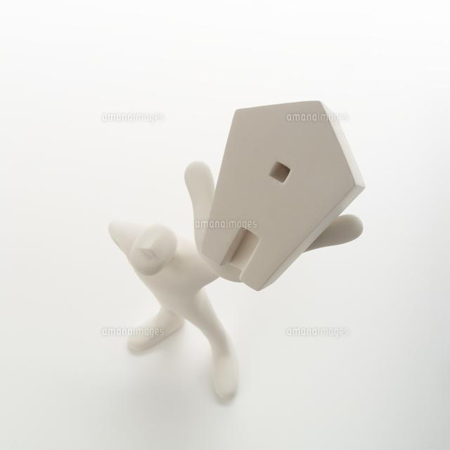 左手に家を掲げて立つ人のオブジェ クラフト (c)visual supple /amanaimages