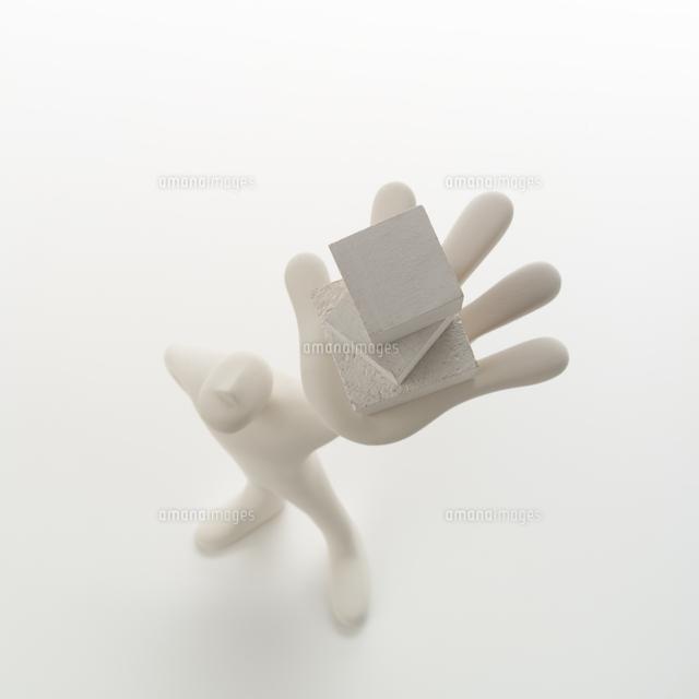 左手に重ねた箱を持って立つ人のオブジェ クラフト (c)visual supple /amanaimages