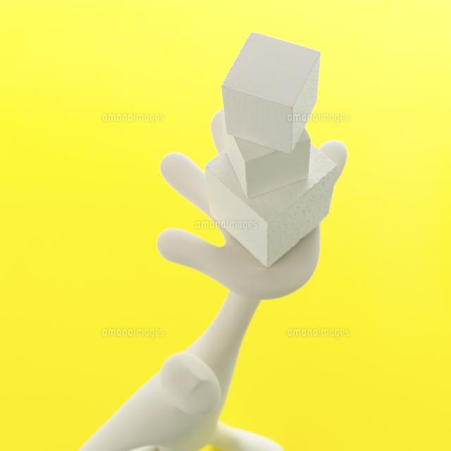 重ねた箱を左手に掲げたオブジェと黄 クラフト (c)visual supple /amanaimages