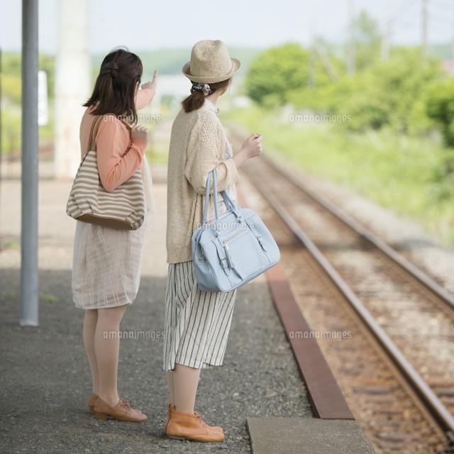 駅のホームで電車を待つ2人の女性 (c)visual supple
