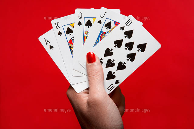 Womans hand holding hand of cards