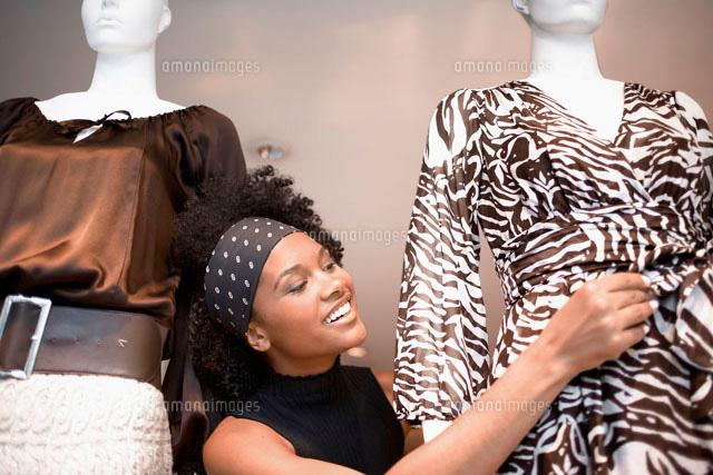 Woman adjusting dress on mannequin (c)clover/a.collectionRF