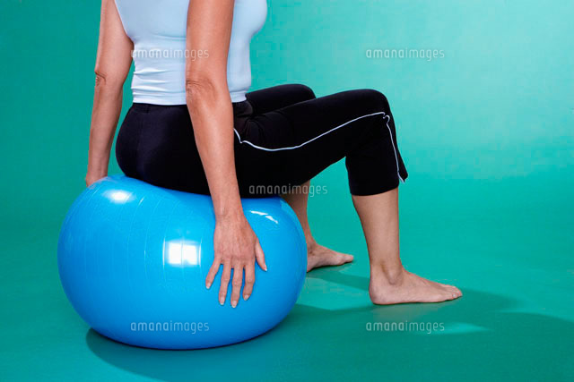 Mature woman sitting on Swiss ball