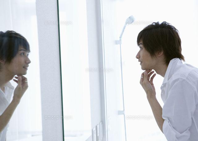 鏡を見る若い男性 (c)イメージナビ
