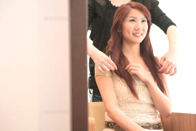 髪の毛を整える美容師と20代女性 (c)didi
