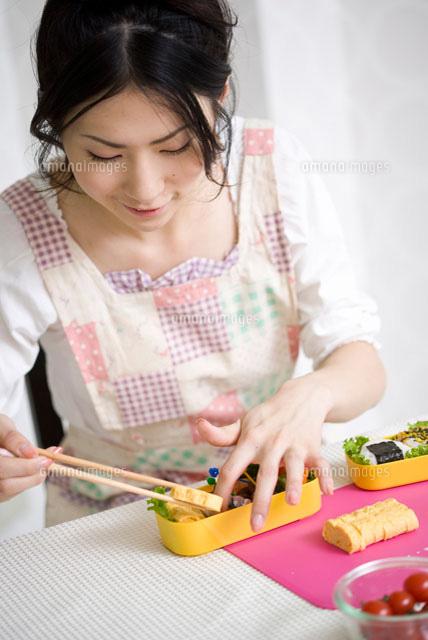 お弁当箱におかずを詰める女性 (c)didi