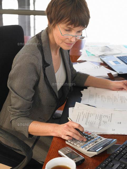 Businesswoman sitting at desk (c)John Rowley
