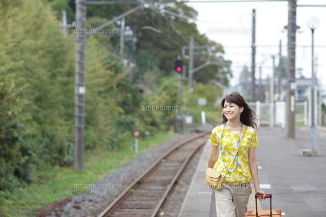 スーツケースを引いてホームを歩く一人旅の女性[11038008284 ...