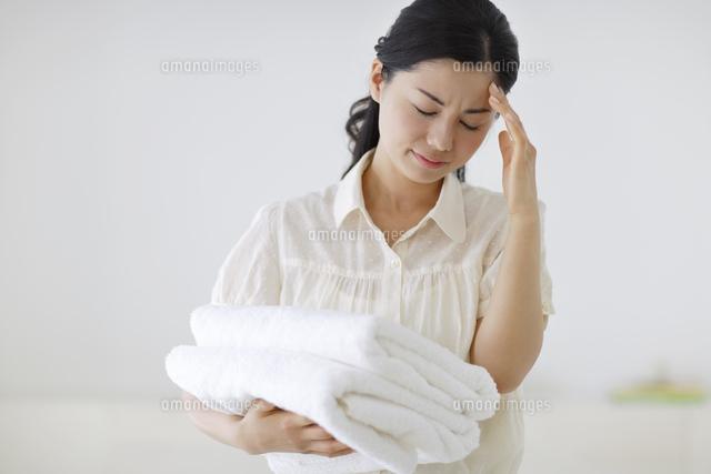 家事の途中に頭痛で苦しむ若い女性 (c)mon printemps