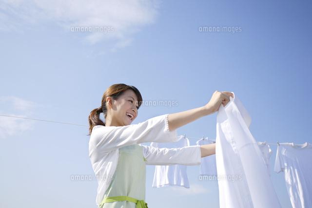 青空の下で家族の洗濯物を干す女性 (c)mon printemps