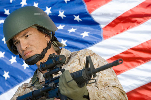 Soldier holding rifle in front of United States flag  (por