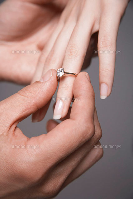 Man placing engagement ring on womans finger  close-up of (c)moodboard