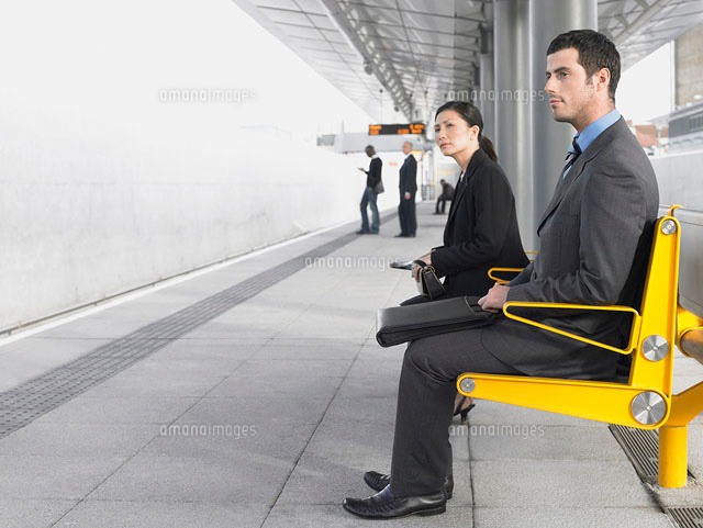 Businesspeople sitting on benches  Waiting at Train Statio
