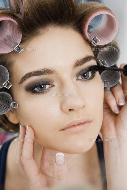 Model in Hair Curlers Having Makeup Applied (c)moodboard