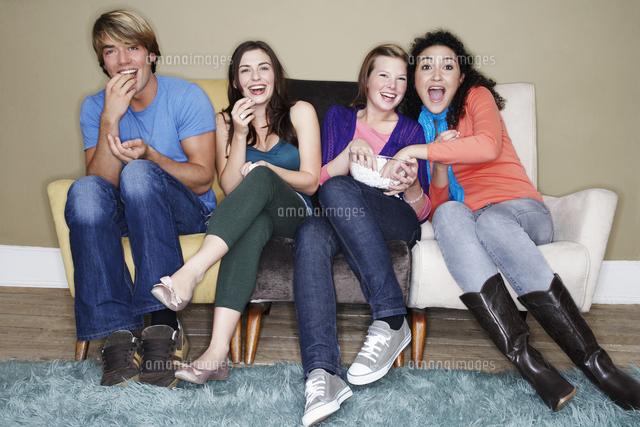 Friends sitting eating popcorn watching movie on sofa (c)moodboard