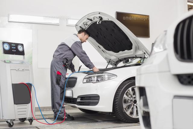 Full length of male engineer examining car in automobile repair shop (c)moodboard