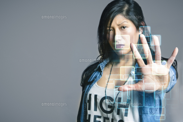 Serious mid adult woman touching futuristic computer screen over gray background