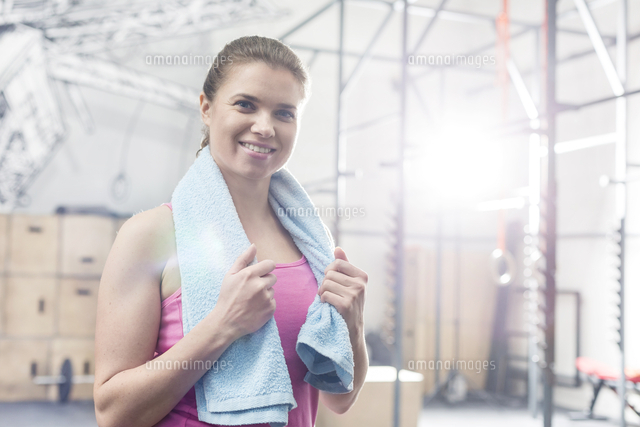 Portrait of happy woman holding towel around neck in crossfit gym (c)moodboard