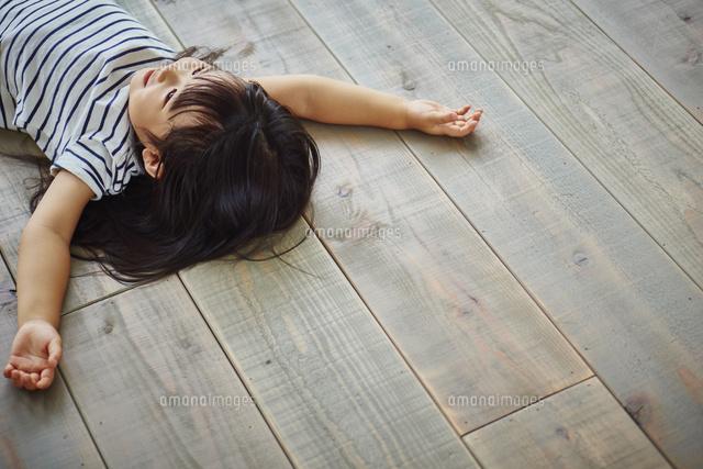 フローリングの床に寝転ぶ女の子 (c)hi-bi